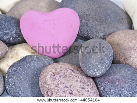 a Pink heart of stone between multi colored natural stones - stock photo