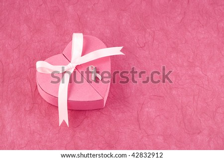 A pink heart shaped box with ribbon and breast cancer awareness pin, pink textured background with plenty of room for copy space, horizontal - stock photo