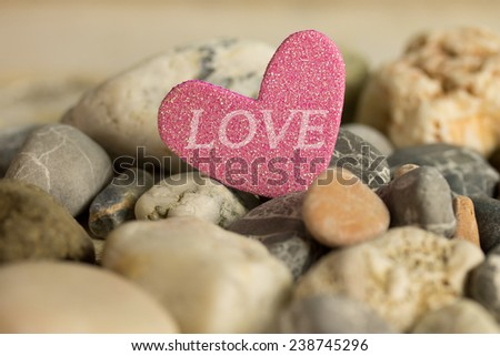 a pink heart with the text LOVE laying between stones - stock photo