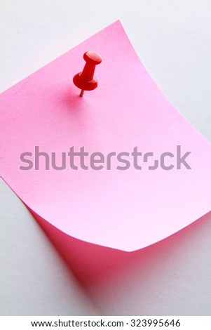 A pink memo note with a red pin on blue - stock photo