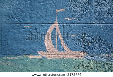 A pink sailboat painted on a blue brick wall.