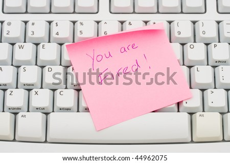 A pink sticky note sitting on a computer keyboard,You are fired - stock photo