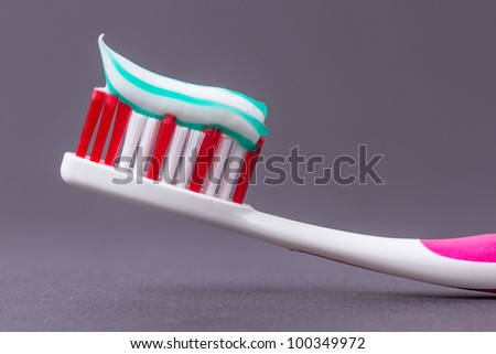 A pink toothbrush with toothpaste on a grey background