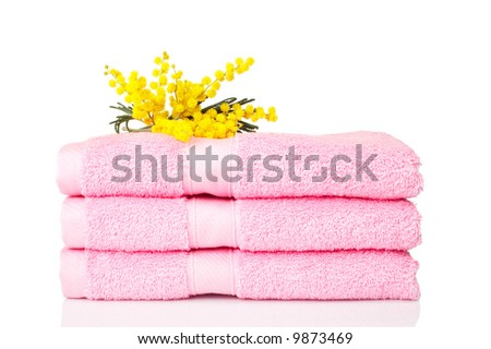 A pink towels stacked with yellow flowers reflected on white background - stock photo