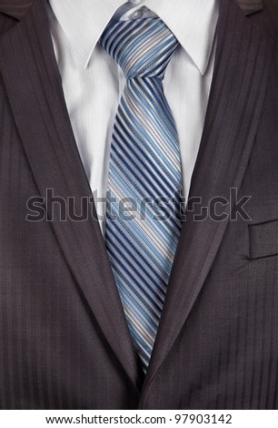 A pinstriped charcoal grey men's business suit with a silk tie and plain shirt - stock photo