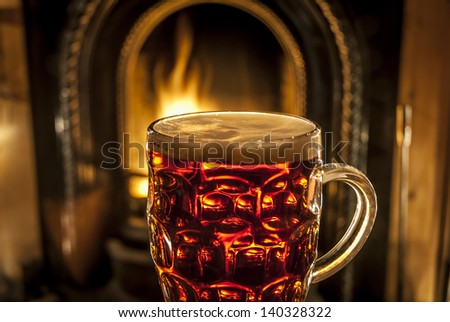 A pint of beer illuminated by a warming fire. - stock photo
