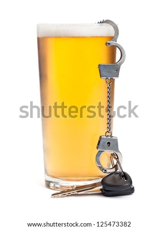A pint of beer with a miniature pair of handcuffs holding a set of keys.