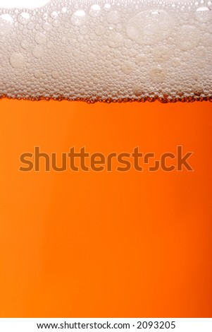 A pint of beer with lots of frothy bubbles - stock photo