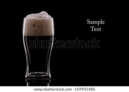 A Pint of Dark Beer on a Black Background. Copy Space - stock photo