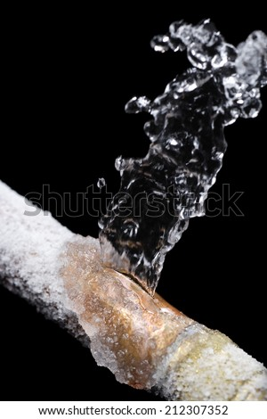 A pipe leaking with freeze damage - stock photo