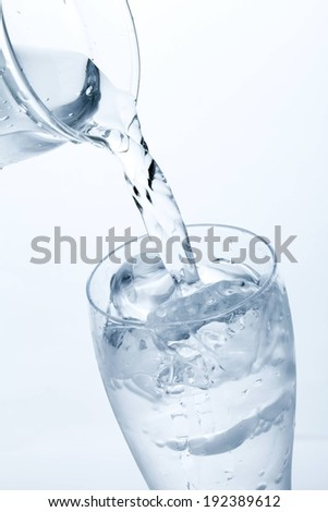 A pitcher being poured into a glass of ice and water. - stock photo