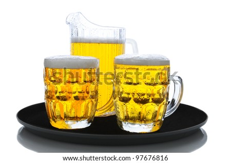 A pitcher of beer and two full glasses on a serving tray over a white background. - stock photo