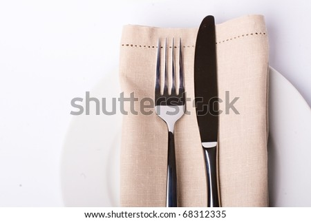A place setting with silver fork and spoon, white dinner napkin, and white china plat - stock photo