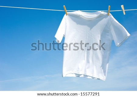 A plain white T-shirt hanging on a clothesline on a beautiful, sunny day, add text or graphic to shirts or copy space - stock photo