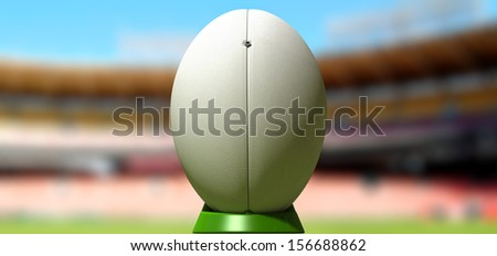 A plain white textured rugby ball on a green kicking tee in a stadium  - stock photo