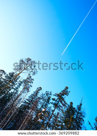 A plane flying high in the sky over winter forest. - stock photo