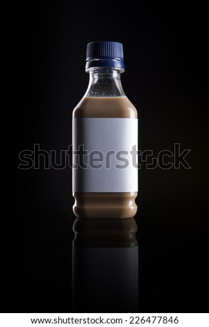 A plastic bottle with coffee(cafe late) with blank label reflective bottom isolated black. - stock photo