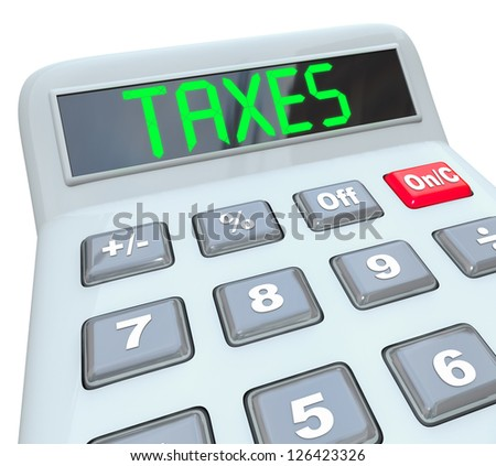 A plastic calculator displays the word Taxes symbolizing the need to file annual tax returns - stock photo