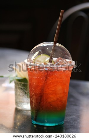 A plastic glass of soft drink with ice cubes. - stock photo