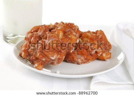 A plate of apple fritters and a glass of milk on a white table setting - stock photo