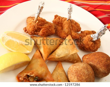 A plate of Arabian kubbe (meatballs), breaded and fried chicken wings,  and samosa pastries which are commonly served as appetisers in the middle east.