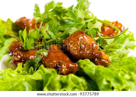 A plate of barbecue buffalo wings garnished with green leaf lettuce and cilantro. - stock photo