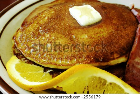 A plate of blueberry pancakes with a slice of fried scrapple. - stock photo