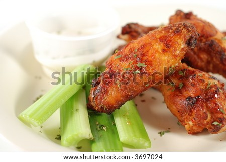 a plate of buffalo wings with celery and blue cheese