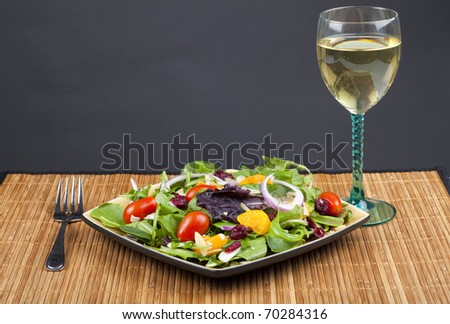 A plate of California salad containing oranges, dried cranberries, red onion, mixed lettuce, sliced almond and miniature tomatoes.  Beside it sits a glass of white wine.