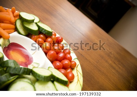 A plate of cherry tomatoes, carrots and cucumber slices. - stock photo