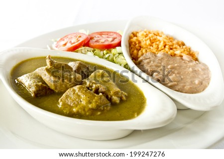 A plate of chili verde with rice and beans. - stock photo