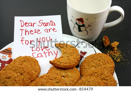 A plate of cookies and a cup of milk, intended for Santa, but a bite has been taken out of one of the cookies. A note for Santa has been left by little Cathy. - stock photo