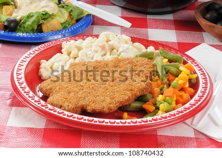 A plate of country fried steak with macaroni salad