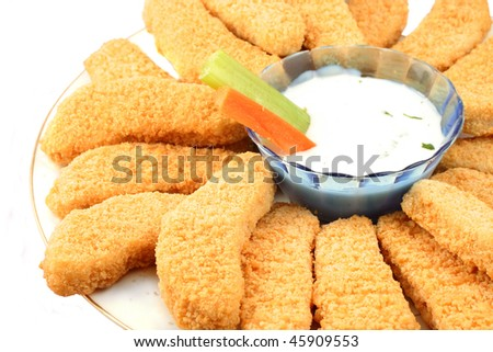 A plate of crispy chicken fingers with  vegetables and dip on a white background - stock photo