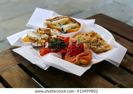 A plate of delicious cicchetti, tapas-like dishes indigenous to Venice, Italy. Sold in many cicchetti bars around town, often with casual street-side seating.