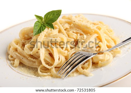 A plate of Fettuccine all'Alfredo, pasta in a butter, cream and parmesan sauce, garnished with a sprig of basil and sprinkled with grated cheese - stock photo