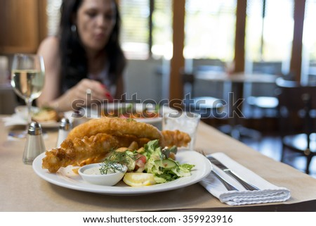 A plate of fish and chips with salad focus on the fish. Shallow depth of field on fish and chips. Out of focus female at the other side of table. Brown paper table cloth. Glass of white wine on table. - stock photo
