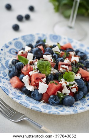 a plate of fruit salad with cheese and a fork in the foreground - stock photo