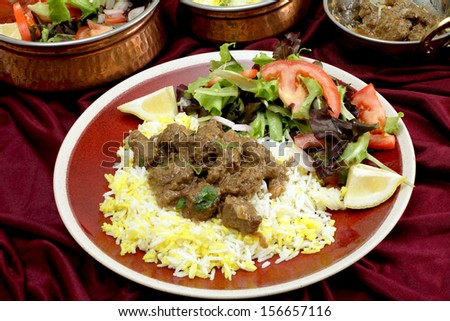 A plate of  homemade beef rogan josh, served with yellow and white rice and a salad, with typical Indian serving bowls behind. Rogan josh is usually made with lamb but works equally well with beef. - stock photo