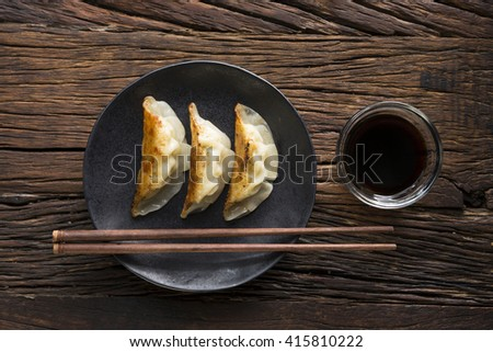 A plate of Japanese gyoza dumplings sitting on a rustic wooden table.  - stock photo