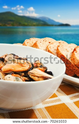 A plate of marinated mussels with the sea shore in the background (shallow dof) - stock photo