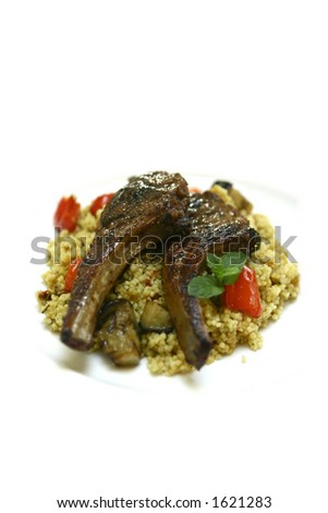 A plate of moroccan couscous with lamb chops isolated on white - stock photo