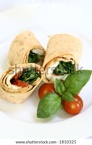 A plate of mozzarella and spinach tortilla wrap sandwich with cherry tomatoes - stock photo