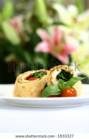 A plate of mozzarella and spinach tortilla wrap sandwich with cherry tomatoes and basil leaves - stock photo