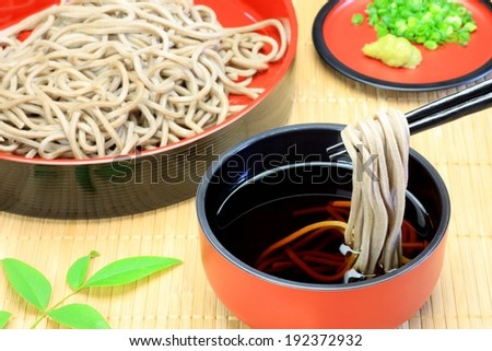 A plate of noodles and a bowl of liquid with chopsticks dipping the noodles. - stock photo