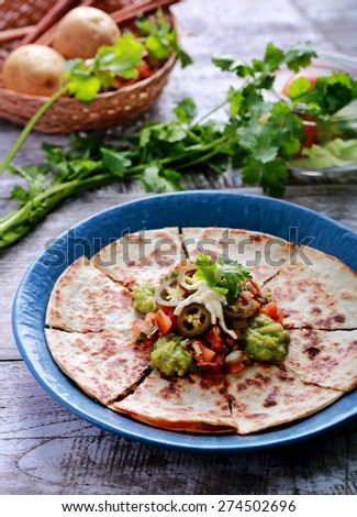 a plate of quesadilla served with salsa, guacamole and jalapenos - stock photo