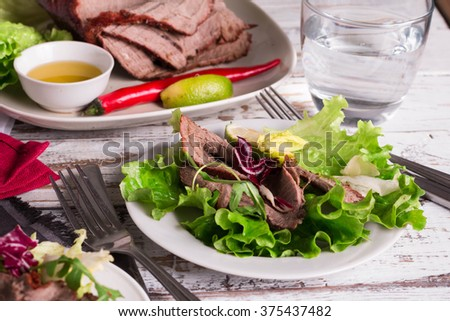 A plate of Roast Beef. Green salad with meat, healthy dinner plate. Selective focus.