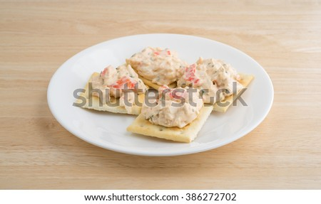 A plate of saltine crackers with lobster snack dip atop a wood table top. - stock photo