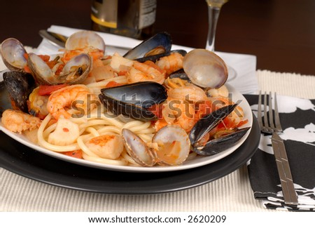 A plate of seafood pasta made with bucatini pasta - stock photo