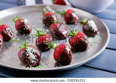 A plate of strawberries in chocolate on blue wooden background